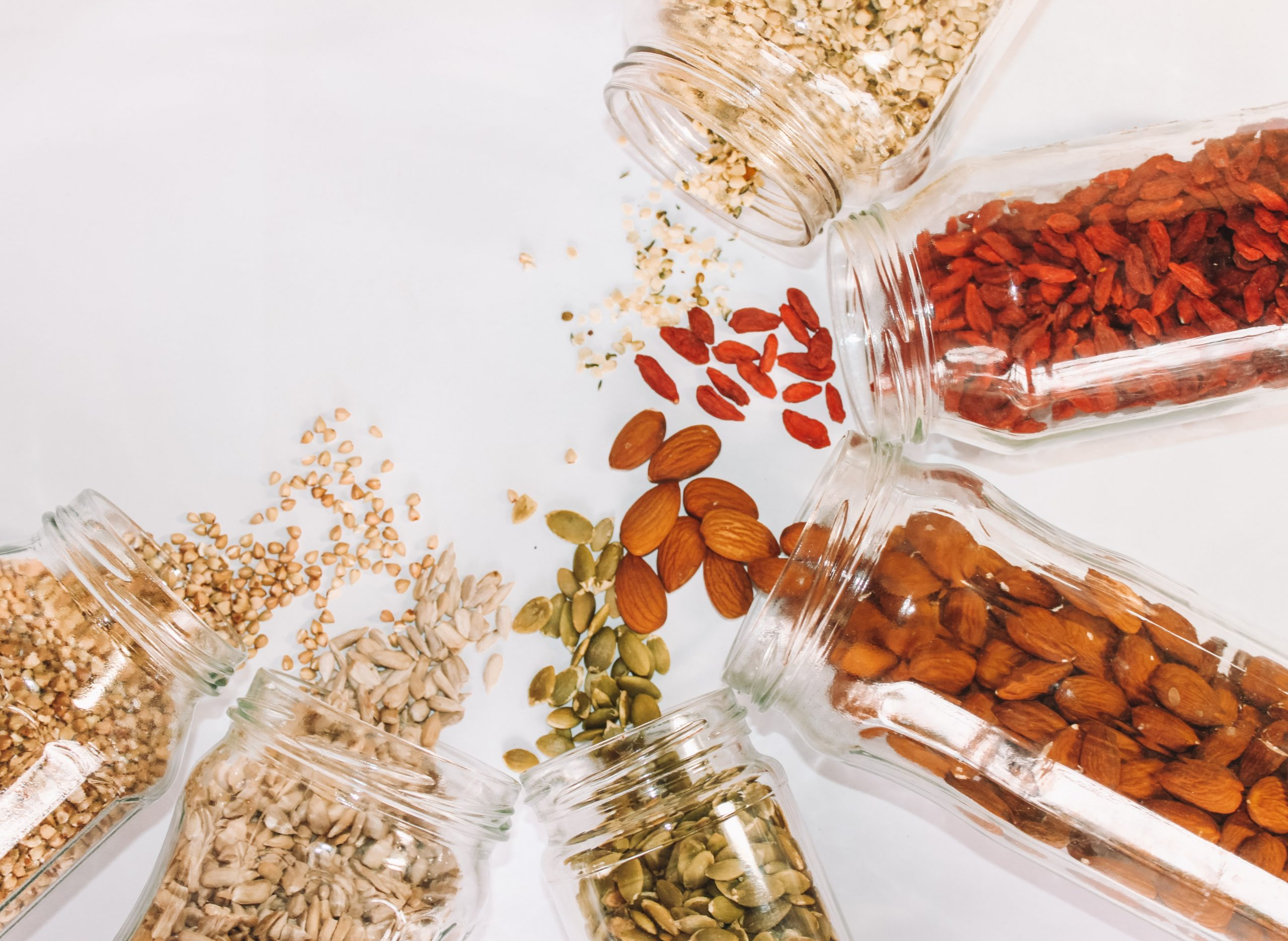 various nuts in jars and strewn on table